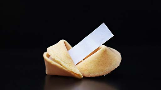 Fortune cookies split in two with a fortune coming out of it